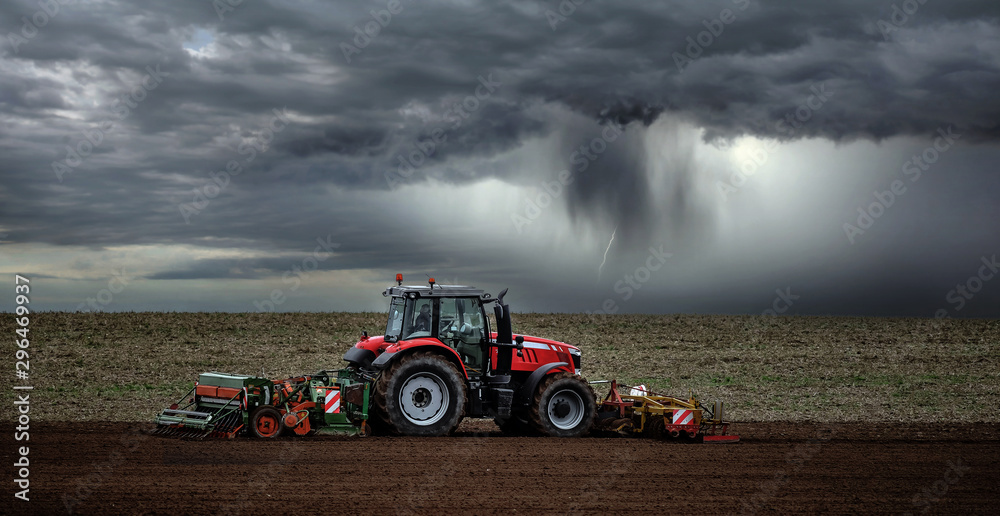 Fototapeta beautiful landscape with a farmer plowing his fields before the storm