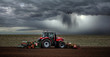 Leinwanddruck Bild - beautiful landscape with a farmer plowing his fields before the storm