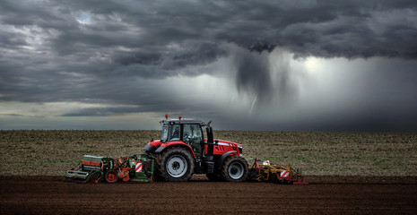 beautiful landscape with a farmer plowing his fields before the storm