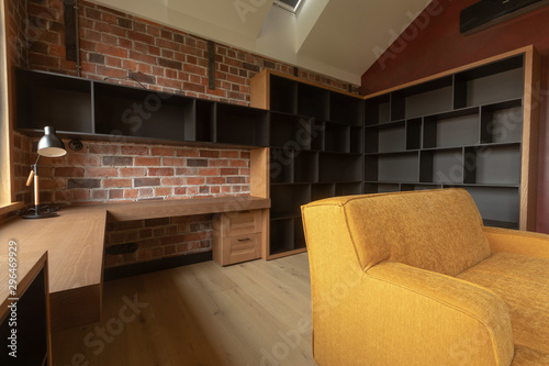 Contemporary Interior Of Light Spacious Living Room With Brown And Black Wooden Furniture And Yellow Sofa Against Red Brick Walls Under Attic Ceiling With Roof Window In Loft Style Buy This
