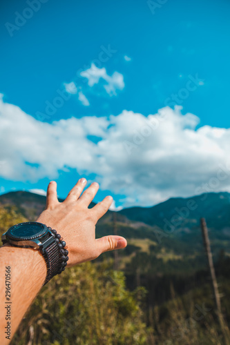 Carta da parati hand with watch and bracelet on the wrist mountains on background