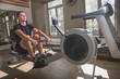 canvas print picture - The athlete is engaged in the gym, the Young man works on the rowing simulator