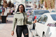City Portrait Of Positive Young Dark Skinned Female Wearing Green Hoody And Eyeglasses Walking At Car Parking.