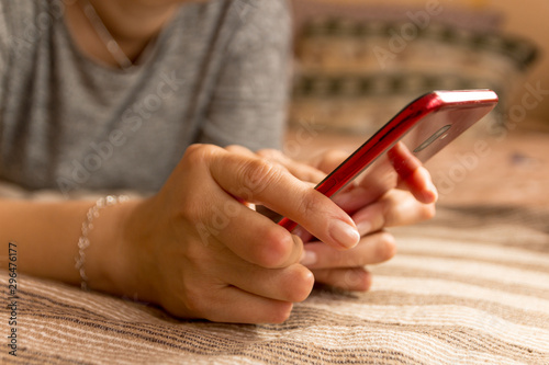 Young woman having rheumatoid arthritis takes a rest sittinng on a bed, looking at her phone at home Slika na platnu