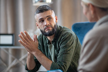 Man Looking At Psychologist Telling Him About Stress