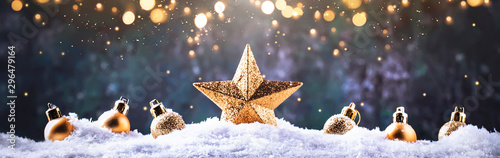 Christmas background with golden star. New Year's decor. Christmas balls in smowdrifts and golden bokeh lights