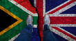 canvas print picture - Business man stands on cracked flag of UK and South Africa. Political concept