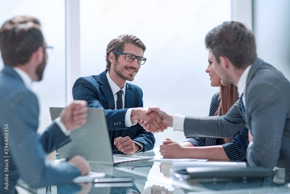 Fototapeta business partners reach out to each other for a handshake