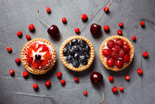 Three Tasty Summer Desserts On The Gray Background Decorated With Wild Strawberries And Cherries. Strawberry Tart, Blueberry Tart And Raspberry Tart.
