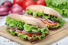 Two Sandwiches With Fresh Vegetables, Ham And Cheese In Ciabatta Bread