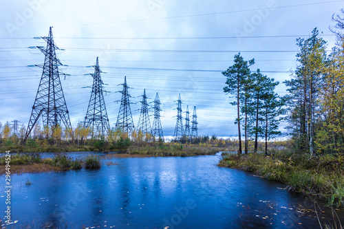 Towers of electric main with the wires in the autumn countryside swamp on the ba Wallpaper Mural
