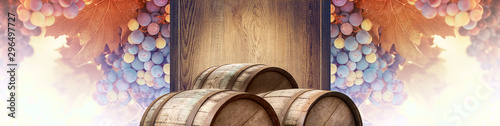 Wine background with a wooden signboard, bunches of red grape and oak barrels. Template of billboard with grapevine and old casks for a presentation of alcohol drinks, wine making industry or winery.