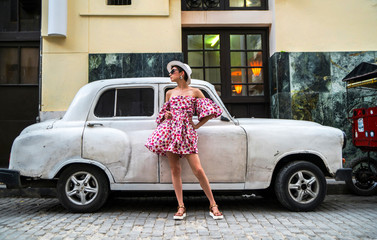 Stylish woman in a bright dress and white hat next to retro car on a city street of Cuba