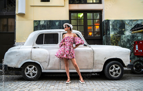 Stylish woman in a bright dress and white hat next to retro car on a city street Wallpaper Mural