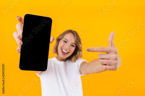 Image of young blond woman pointing finger at smartphone in hand