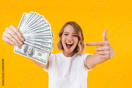 Fototapeta Image of excited blond woman holding bunch of money cash obraz