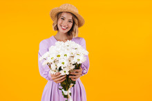 Image Of Content Woman In Elegant Dress And Straw Hat Holding Flowers