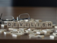 The Concept Of Devilish Represented By Wooden Letter Tiles