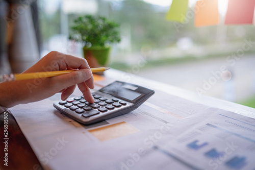 Close up of businesswoman or accountant working on calculator to calculate business data, and accountancy document. Business financial and accounting concept.