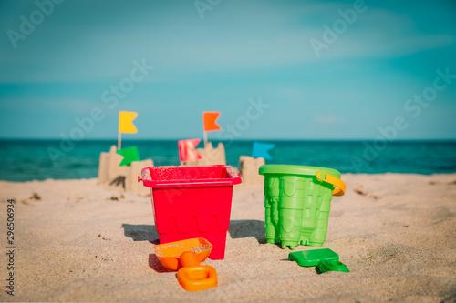 Sand castle on tropical beach and kids toys