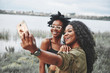 canvas print picture - Two female afro american friends have a walk around beach. Taking selfie