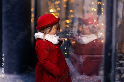 Photographie  emotional child in red look Christmas store window