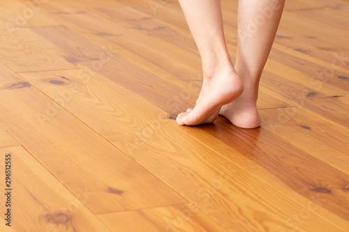 Obraz 木目の床と若い女性の足元のアップ - fototapety do salonu