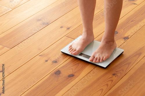 Stampa su Tela  木目の床と体重計に乗る若い女性の足元