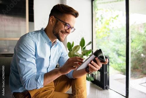 Fotografia  Young smiling Man typing on digital tablet