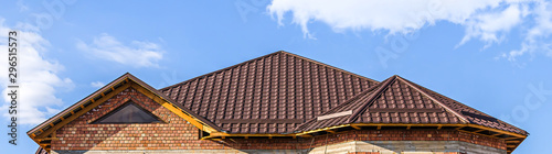 The roof of the house from a metal profile against the sky with clouds Fototapeta