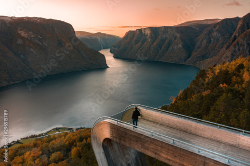 Montage in der Fensternische Lachs A Tourist Looks Over the Norwegian Fjords at Sunset from a Lookout Point in Fall