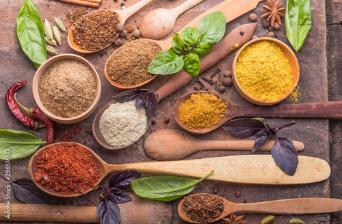 Fotografija Heaps of various ground spices in wooden spoons on wooden background