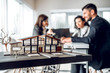 Leinwanddruck Bild - Close up image of house model with group business people on blurred background in building design studio. Architecture project concept