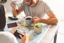 Happy Couple Planning Next Travel Destination Using World Map - Young Playful People Having Fun And Getting Ready For Vacation - Relationship And Traveling Lifestyle Concept