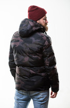 Hipster Winter Fashion. Guy Wear Hat And Black Winter Jacket. Comfortable Winter Outfit. Winter Stylish Menswear. Man Stand Warm Camouflage Pattern Jacket Parka With Hood Isolated On White Background