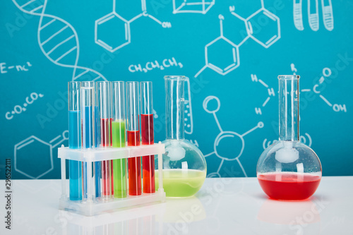 Fotomural  glass test tubes and flasks with colorful liquid on blue background with molecul