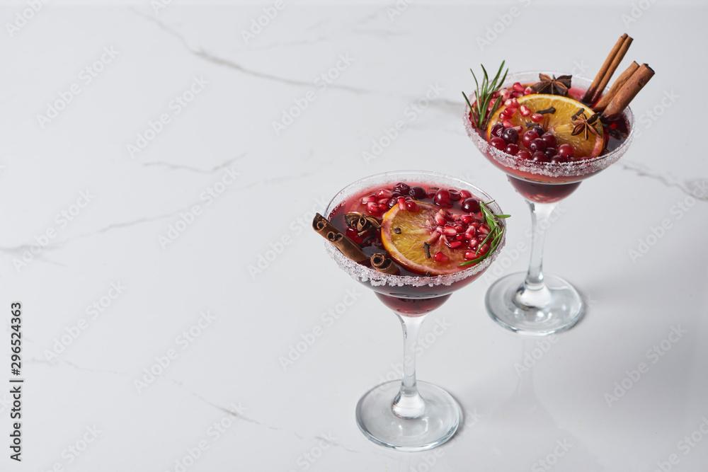 Fototapeta christmas cocktail with orange, pomegranate, cinnamon on marble table