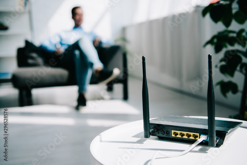 selective focus of black plugged router on white table and businessman sitting o Wallpaper Mural