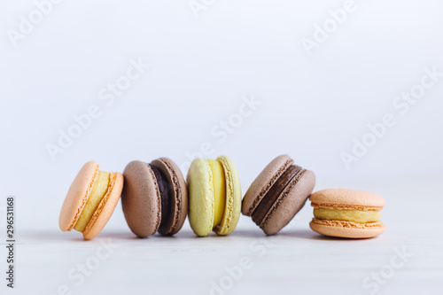 Montage in der Fensternische Macarons Tasty French macarons on a white wooden table. Multicolored macarons. White background.