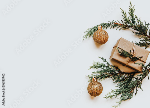 Canvastavla  Bright green twigs of pine tree and a light brown gift box and golden balls on the white background