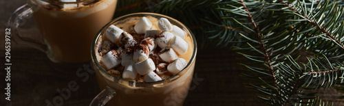 panoramic shot of cacao with marshmallow and cacao powder in mugs near pine bran Canvas Print