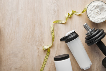 top view of heavy dumbbell near sports bottle and measuring tape on wooden surface