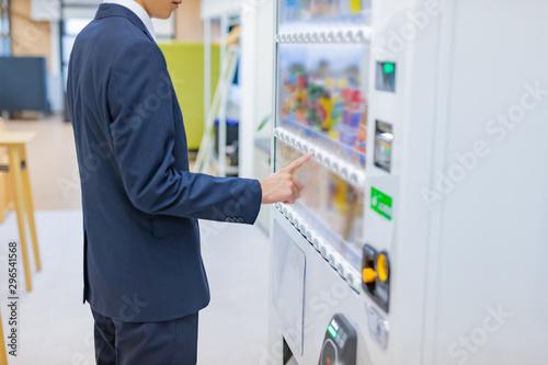 Obraz ビジネスシーン 自動販売機で飲み物を購入するビジネスマン - fototapety do salonu