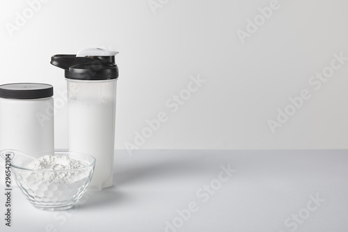 sports bottle with protein shake near jar and protein powder on white