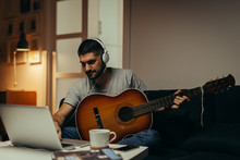 Man Playing Guitar At His Home. Using On Line Lessons