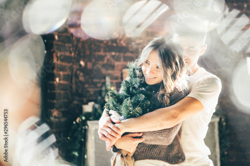 Woman holding small Christmas tree and hugging with her boyfriend in dark decorated room Tableau sur Toile