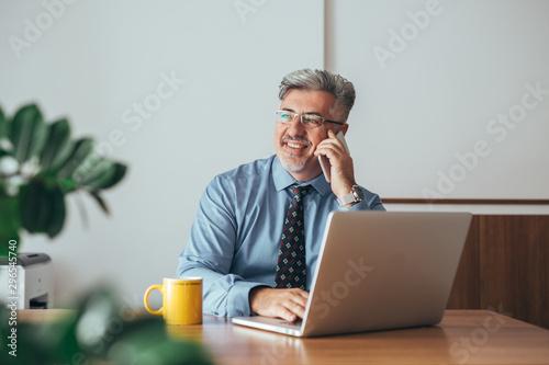 Fototapety, obrazy: senior manager using mobile phone sitting desk in his office