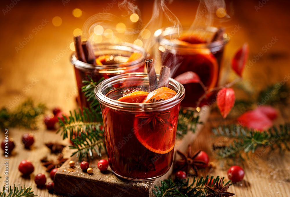 Fototapeta Christmas mulled red wine with aromatic spices and citrus fruits on a wooden rustic table, close-up. Traditional hot drink at Christmas time