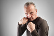 Elderly stylish man in boxing pose with strong face holds blow of fate, fights with life difficulties and problems on white studio background