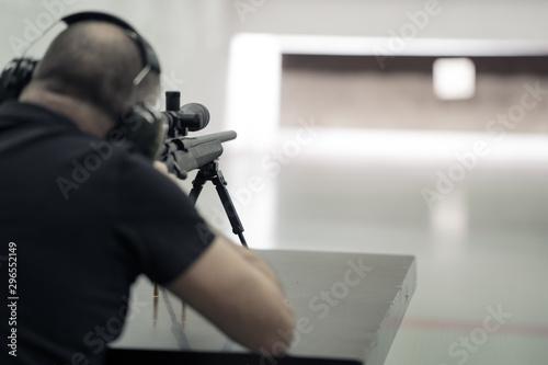 Fotomural  Scharfschütze Mann von hinten zielt auf Zielscheibe geblurrt Var
